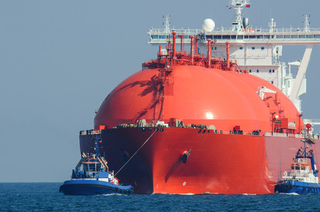 LNG TANKER AT SEA. Large tanker flows for the escort tugs Standard-Bild