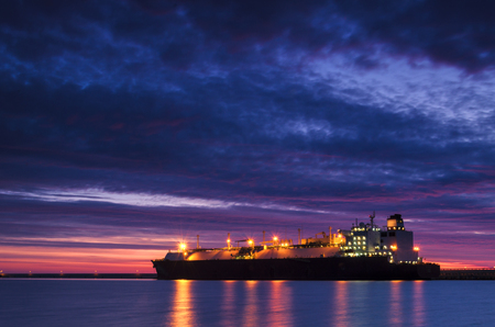 LNG TANKER AT THE GAS TERMINAL - Sunrise over the sea Stock Photo