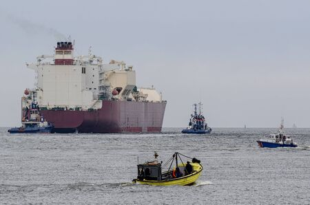 maneuvering: LNG TANKER AND YELLOW BOAT FISH - Border guards Assists and tugs on a big ship sailing on a cruise