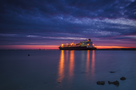 LNG CARRIER IN PORT - Sunrise over the sea Stock Photo
