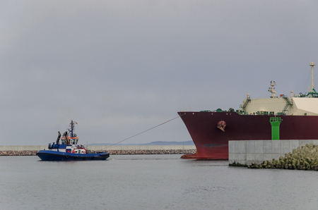 asserts: GAS CARRIER AND TUG - The tugboat asserts to sail from the port of the big ship Stock Photo