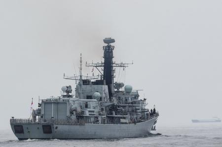 BRITISH FRIGATE - Een oorlogsschip op een patrouille in de zee Stockfoto - 83093634