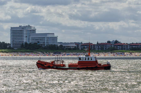 PILOT BOAT - Against the background of the sea coast and the buildings of Swinoujscie Stock Photo - 84076099