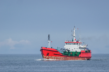 merchant: TANKER - The red ship sails into the sea Stock Photo