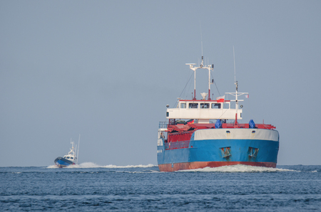 A merchant vessel and a speed boat on the water