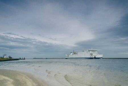 A ferry docking at a harbor by the beach