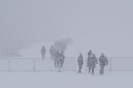 WINTER ATTACK - People walking through the blizzard Stock Photo