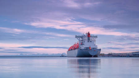 LNG TANKER AT THE GAS TERMINAL - Sunrise over the ship and port Stock Photo