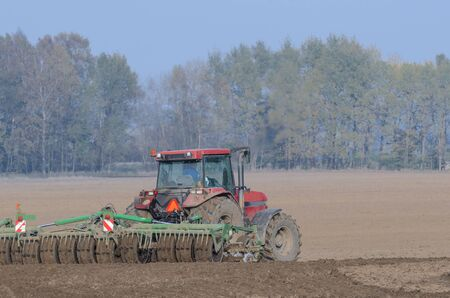 FARM - Tractor while working on a plowed field