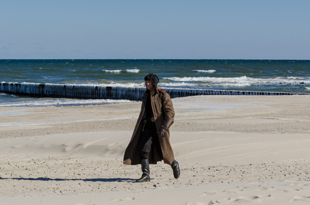 KOLOBRZEG, WEST POMERANIAN / POLAND - 2018: Reconstruction of battle for Ko?obrzeg - A Red Army soldier in uniform uniform marches on a sea beach Фото со стока - 110653568