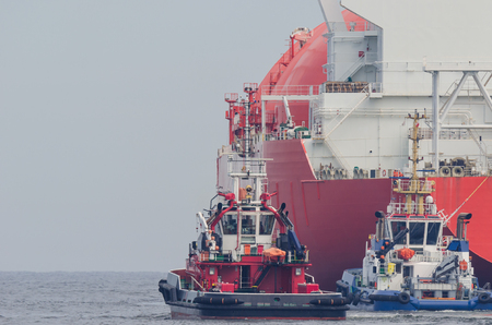 LNG TANKER - Fireboat and Tugs next to a big red ship Stock Photo