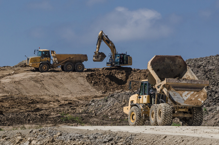 CONSTRUCTION MACHINERY - Dump trucks and excavator on construction side