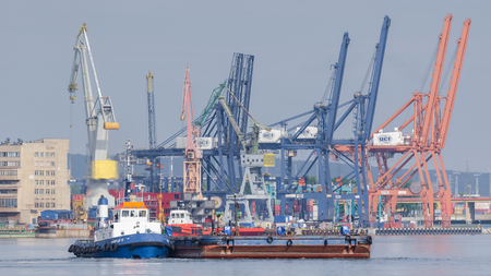 GDYNIA, POMERANIA REGION  POLAND - 2018: Tugboat with a barge maneuvers in the port on the background of cranes and wharves Editorial