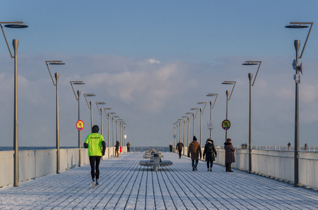 KOLOBRZEG, WEST POMERANIAN  POLAND - 2018: Holidaymakers and patients take a stroll on the winter pier