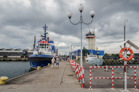 GDYNIA, POMERANIA / POLAND - 2018: A tugboat, a small ship and a traffic traffic control tower at the promenade Editorial