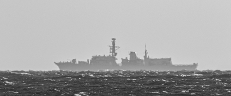 STORMY SEA - Outline of a warship on the horizon