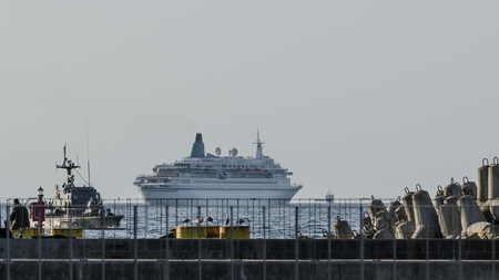 NAVIGATION LIGHT - Infrastructure of sea port in Kolobrzeg and a cruise ship in the roadstead Standard-Bild - 115728022