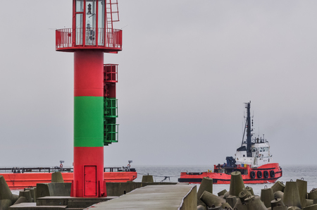 RED TUGBOAT ON ROADSTEAD - A small ship departs from the port of Swinoujscie by towing a barge