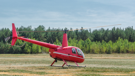 HELICOPTER - A small red machine takes off from the airport
