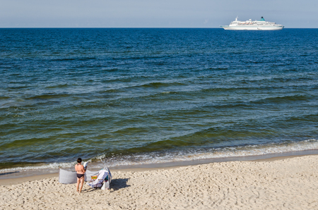REST ON THE SEA BEACH - People on the golden sand and cruise ship