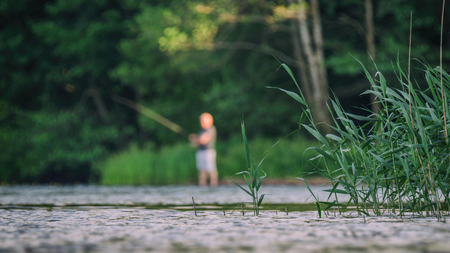 ANGLER - A man with a fishing rod on the edge of the lake Imagens