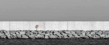 SEAPORT BREAKWATER - Concrete wall, stones and lifebuoy