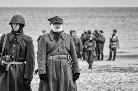KOLOBRZEG, WEST POMERANIAN / POLAND - 2019: Reconstruction of battle for Kolobrzeg - A Polish soldier on a sea beach with a bandage