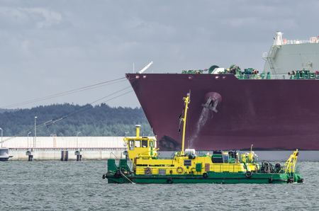 LNG TANKER - Ship moored to the gas terminal and dredger at work