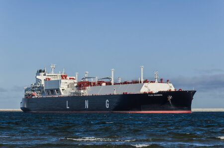 SWINOUJSCIE, WEST POMERANIAN  POLAND - 2019: LNG tanker with gas cargo maneuvers at port wharf for mooring at the gas terminal