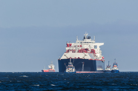 LNG TANKER - A large ship belayed by tugboats travels by water to the port
