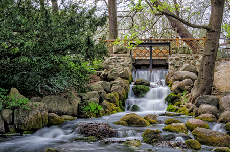 FOOTBRIDGE OVER THE STREAM - A small waterfall in a city park