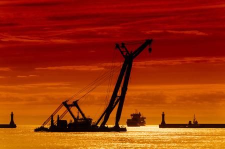 SEA CRANE - A large floating machine is being manned in a port