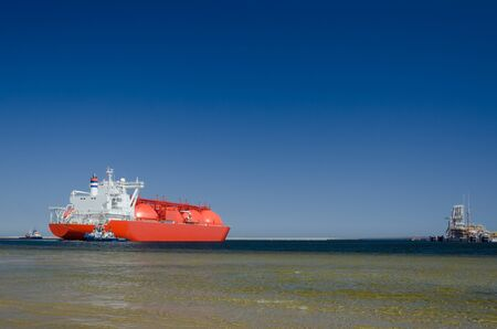 GAS TANKER - The big ship maneuvers in the mooring port at LNG terminal