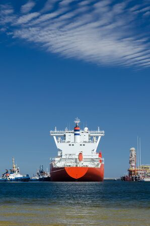 GAS CARRIER AND LNG TERMINAL - The big ship maneuvers in the mooring port at the wharf Stockfoto