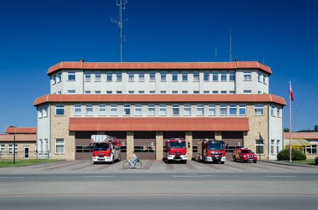 KOLOBRZEG, WEST POMERANIAN / POLAND - 2019: National Firefighting Rescue System - Fire station and rescue vehicles in front of garages Imagens - 128080843