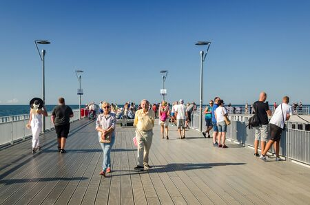 KOLOBRZEG, WEST POMERANIAN  POLAND -2019: Holidaymakers are walking around the pier on a sunny summer day