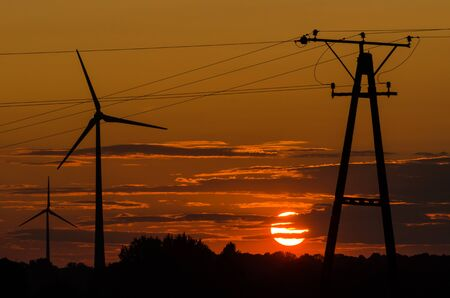 WIND FARM AND POWER POLE OF AN ELECTRICITY TRANSMISSION LINE - Hot evening landscape over the fields
