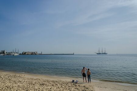 SUMMER BY THE SEA - Two people on the beach are watching a sailing ship on the way to the port