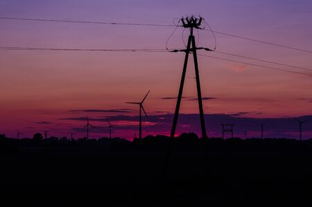 WIND FARM AND POWER POLE OF AN ELECTRICITY TRANSMISSION LINE - Fiery evening over the fields Imagens
