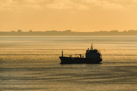 MERCHANT VESSEL ON TE BAY - Sunny morning on the sea coast Imagens