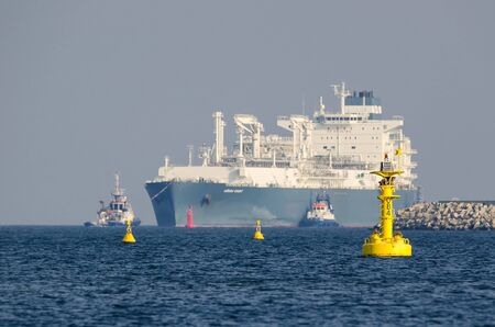 SWINOUJSCIE, WEST POMERANIAN  POLAND - 2019: The gas tanker HOEGH GIANT with the supply of blue fuel is maneuvering on waterway to gas terminal 新聞圖片
