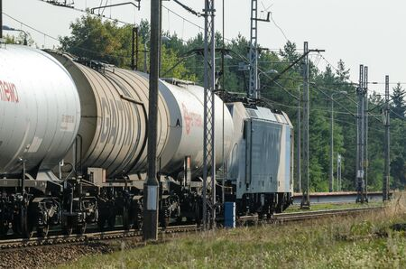 SWINOUJSCIE, WEST POMERANIAN  POLAND - 2019: A modern locomotive on the route pulls a composition of wagons for the transport of chemical materials and petroleum products 報道画像