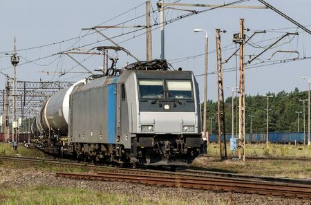 RAILWAY TRANSPORT - A modern locomotive on the route pulls a composition of wagons for the transport of chemical materials and petroleum products Banco de Imagens
