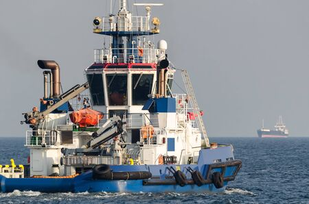 TUGBOAT - A big strong boat and a freighter at sea Banco de Imagens
