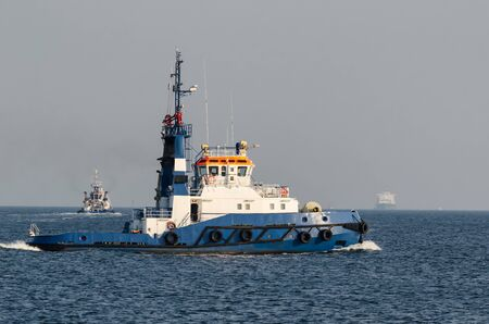 TUGBOAT AND TANKER - A large and strong boat is getting ready to work with the ship
