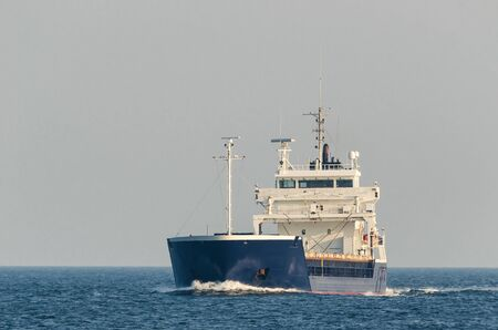 GENERAL CARGO SHIP - Freighter is sailing to the port Stock fotó - 130738562