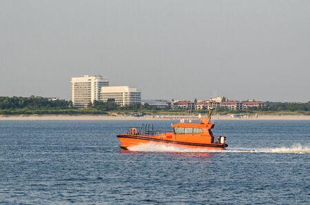 PILOT VESSEL - An orange motorboat is sailing into the port Stock fotó - 130738563