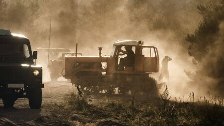 CONSTRUCTION MACHINERY AND MILITARY OFF-ROAD CAR - Heavy vehicles in dust and sunshine