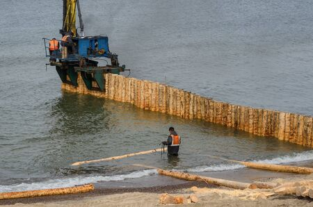 SEA COAST - Workers strengthen the sea shore by building groyne from wooden piles Stock Photo