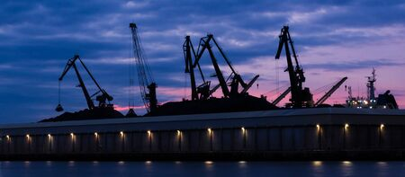 TRANSSHIPMENT TERMINAL - Port cranes on the coal quay in Gdynia at sunrise